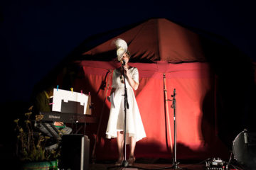 Bride at microphone on wedding day in red tent