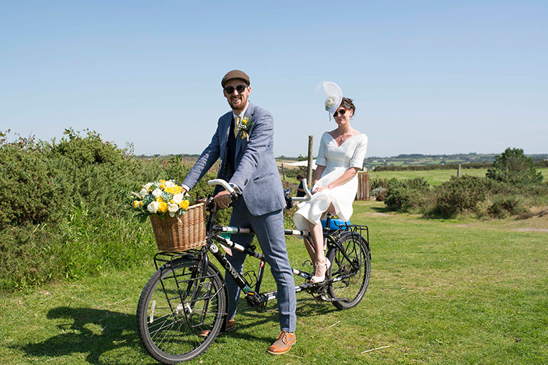 Bride and groom riding a tandem bike in the sunshine on wedding day