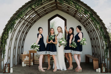 Bride and bridesmaids in wooden wedding arch at Mount Pleasant Eco Park
