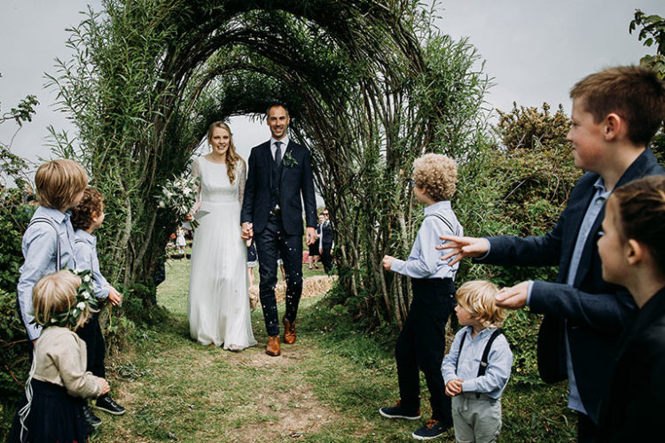 Bride and groom walking through living willow arch on wedding day at Mount Pleasant Eco Park
