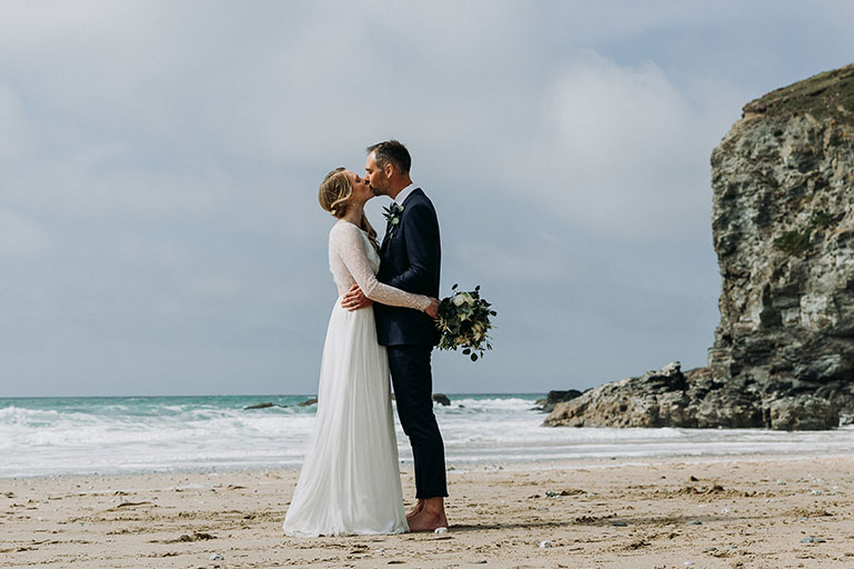 Bride and groom kissing on beach in Cornwall