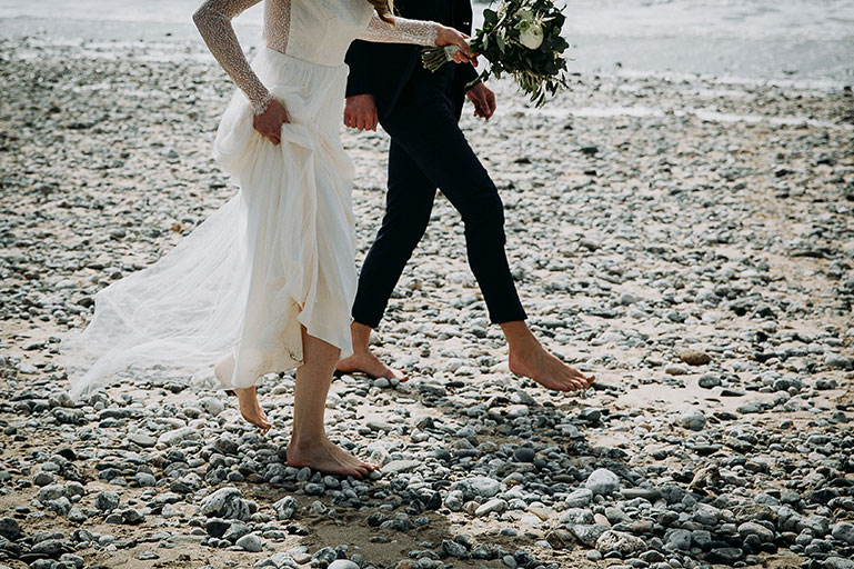 Bride and groom sandy toes on beach on Cornwall wedding day