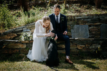 Bride and groom with black labrador dog on wedding day