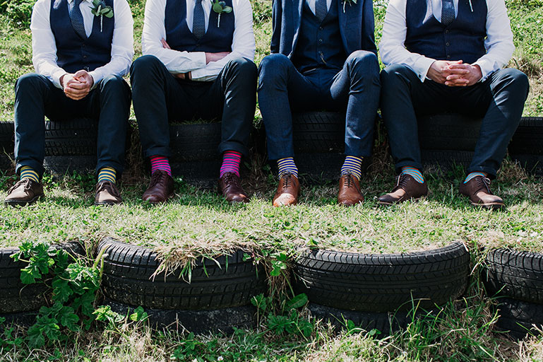 Groom and groomsmen in suits sat on tyres in sunshine