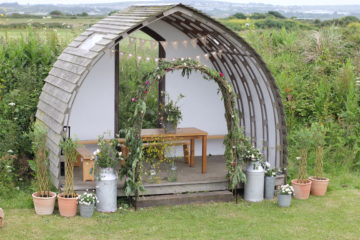 Wooden wedding arch decorated with green natural foliage and flowers for eco wedding