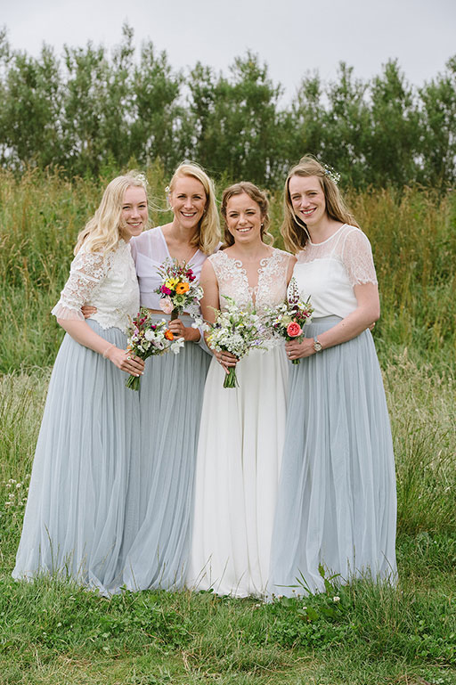 Bride and Bridesmaids in white and blush blue dresses on wedding day