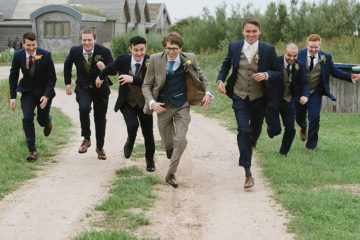 Groom and groomsmen running in tweed suits on wedding day
