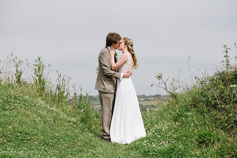 Bride and Groom kissing on wedding day in green countryside