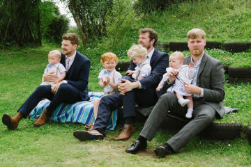Wedding guests with small children sat on tyres