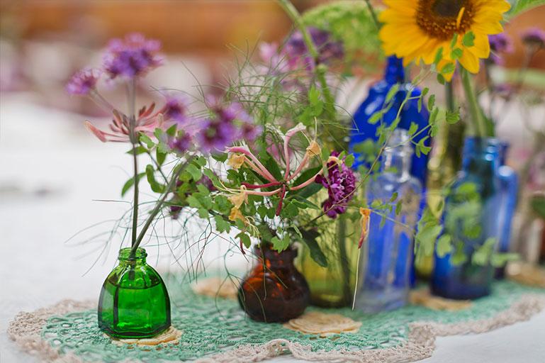 Vintage glass bottles as vases for garden flowers wedding decoration