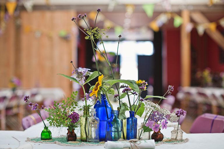 Vintage coloured glass bottles and cottage garden flowers wedding decor