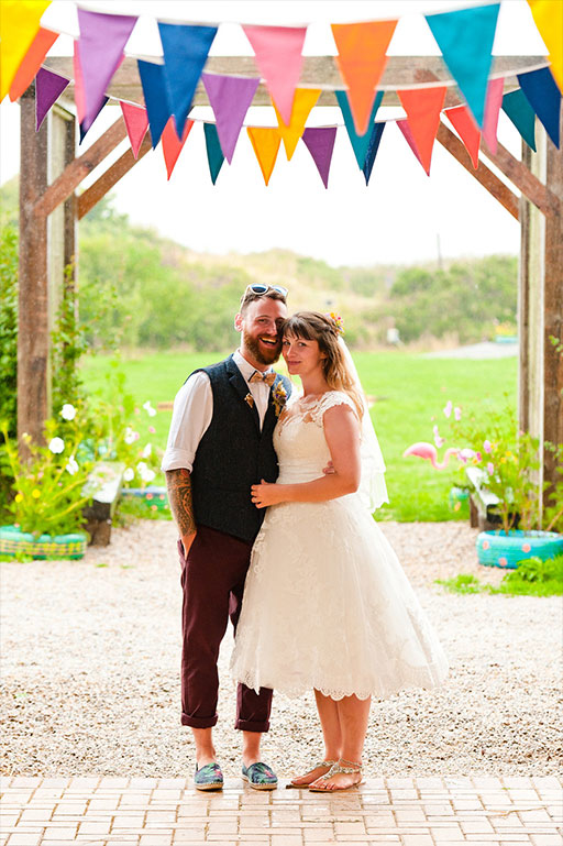 Bride and groom on wedding day beneath colourful bunting decoration