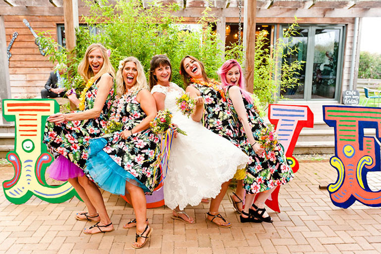 Bride and bridesmaids laughing on wedding day