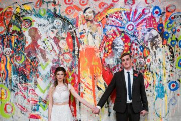 Bride and Groom holding hands in front of brightly coloured backdrop