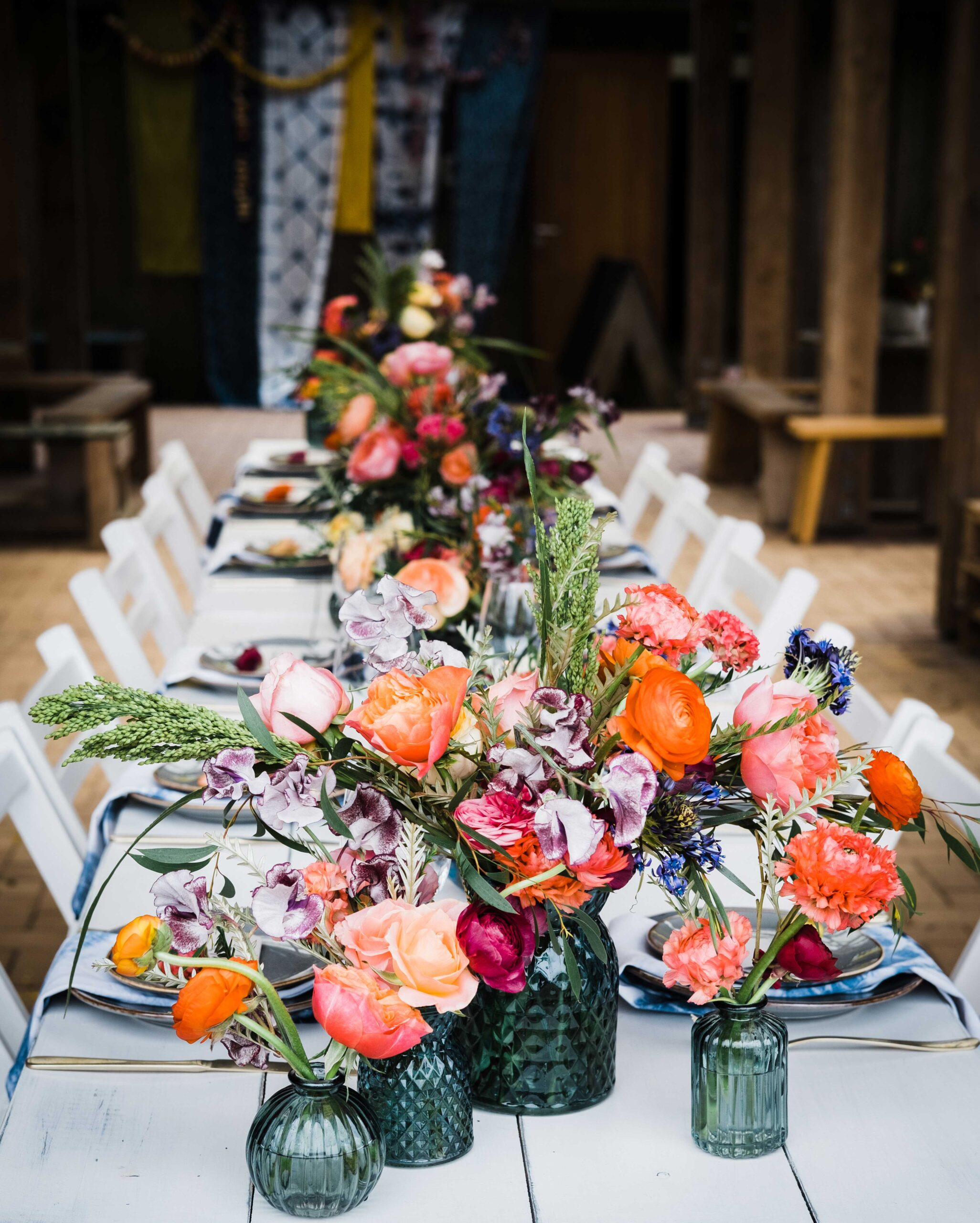 Styled wedding table setting with colour glass jars and bright flowers