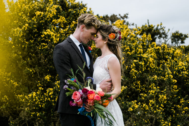 Wedding couple at outdoor boho wedding venue with yellow Cornish gorse