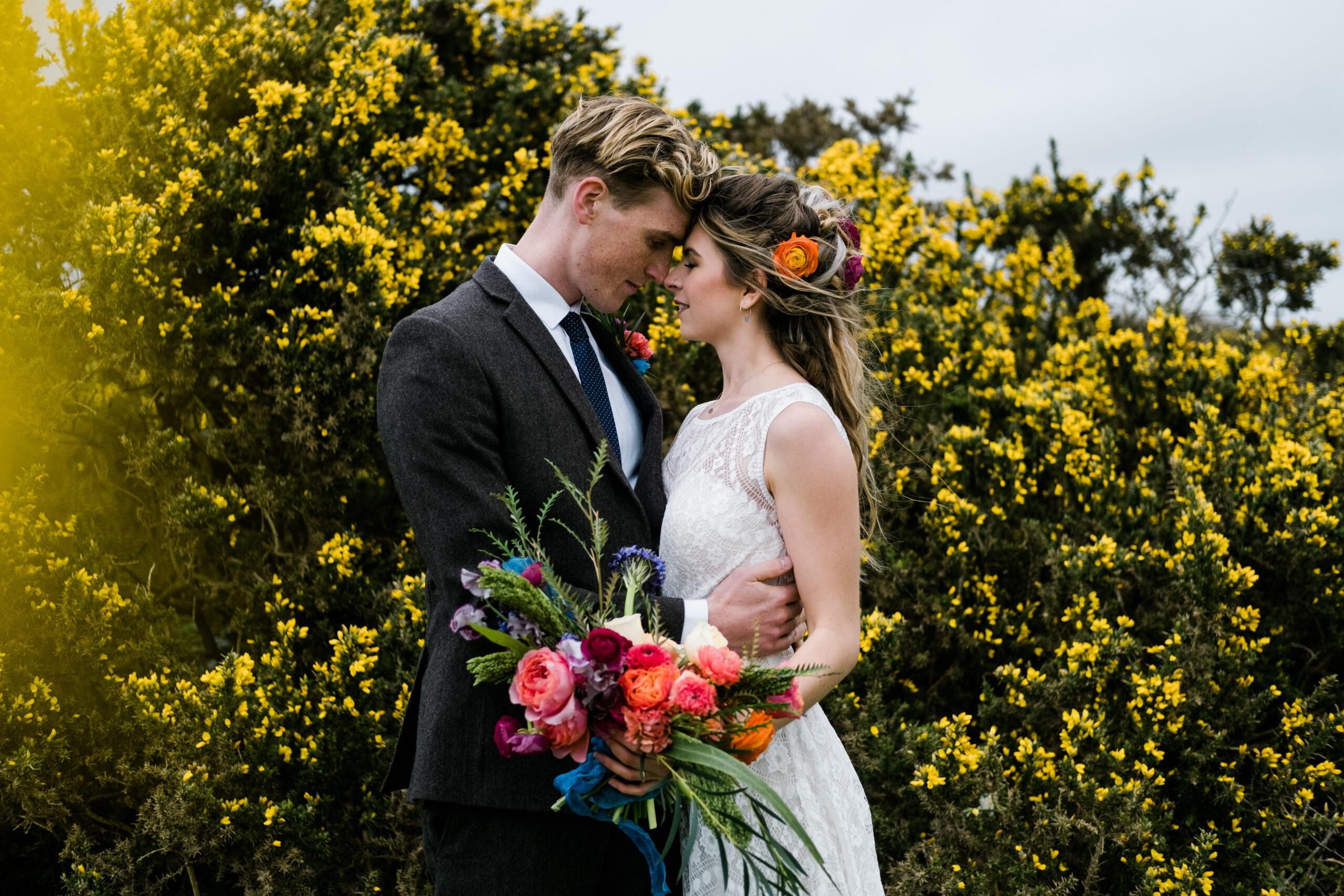 Wedding couple at outdoor boho wedding venue with yellow Cornish gorse