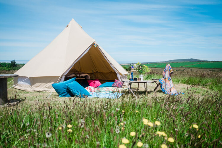 Glamping bell tent set up in Cornwall camping field with blue sky